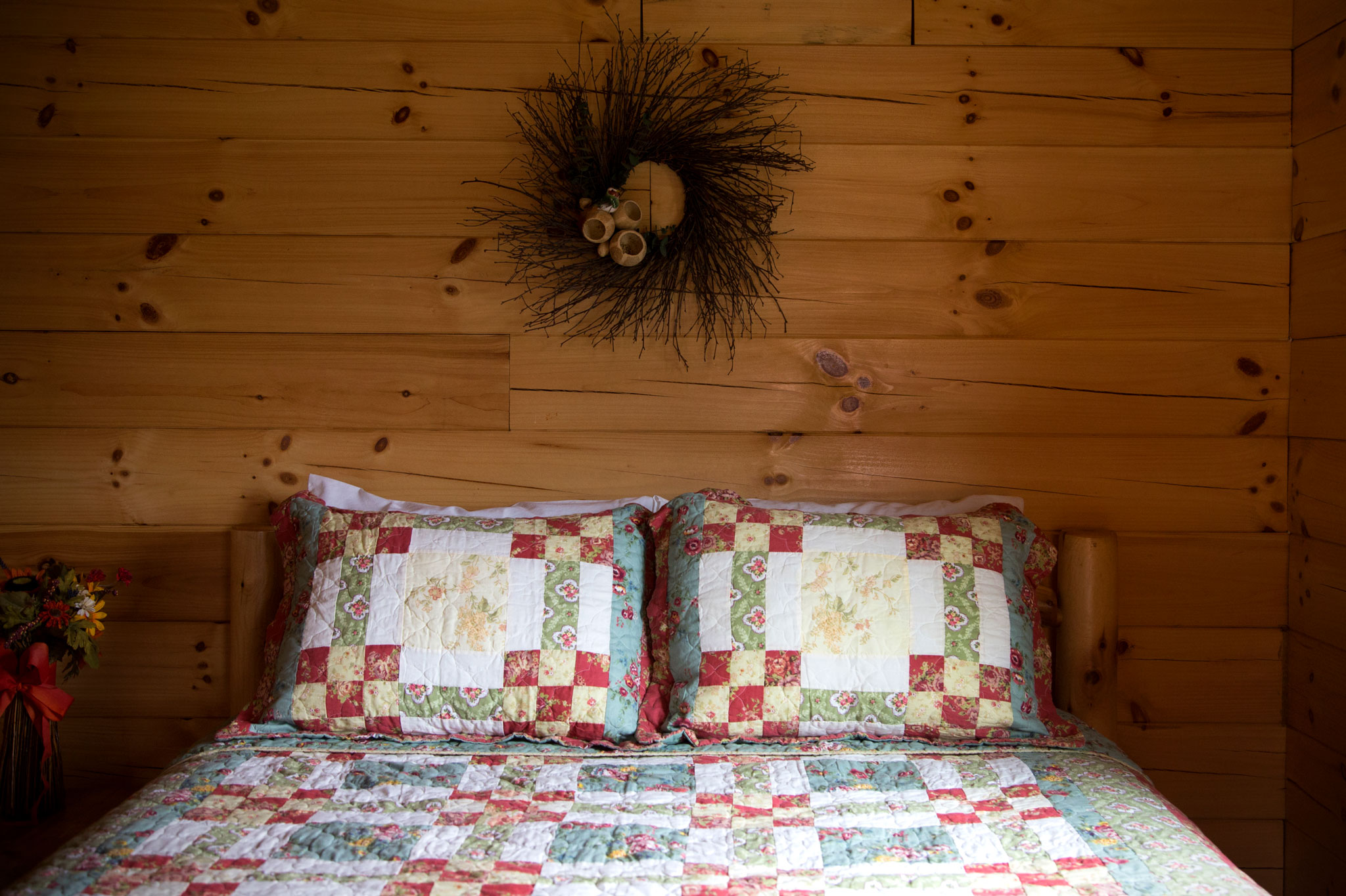 Bed with two pillows covered with quilted blanket. Wooden wall with ornament in background.