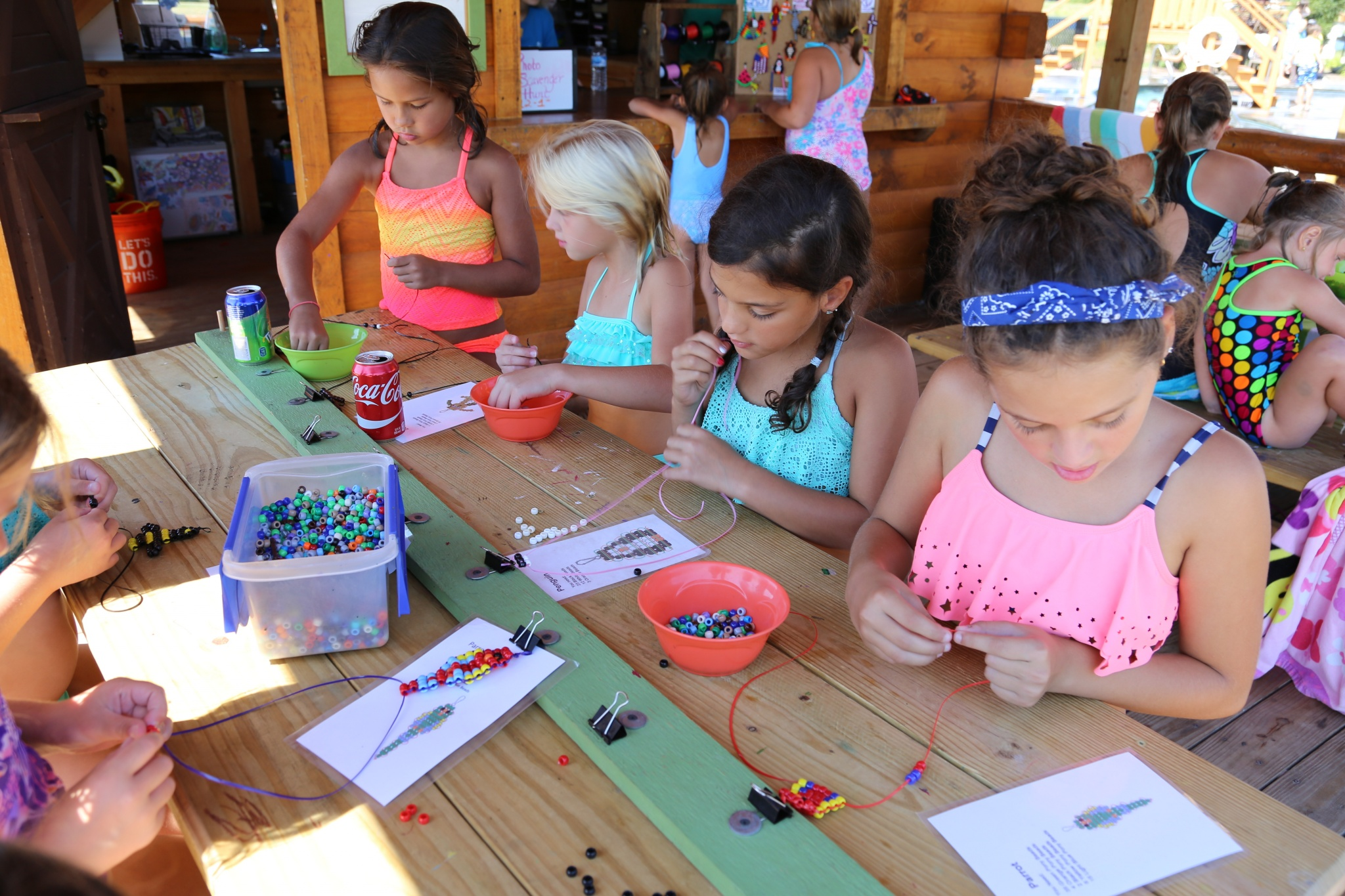 Young girls at an activity table with beads and crafts