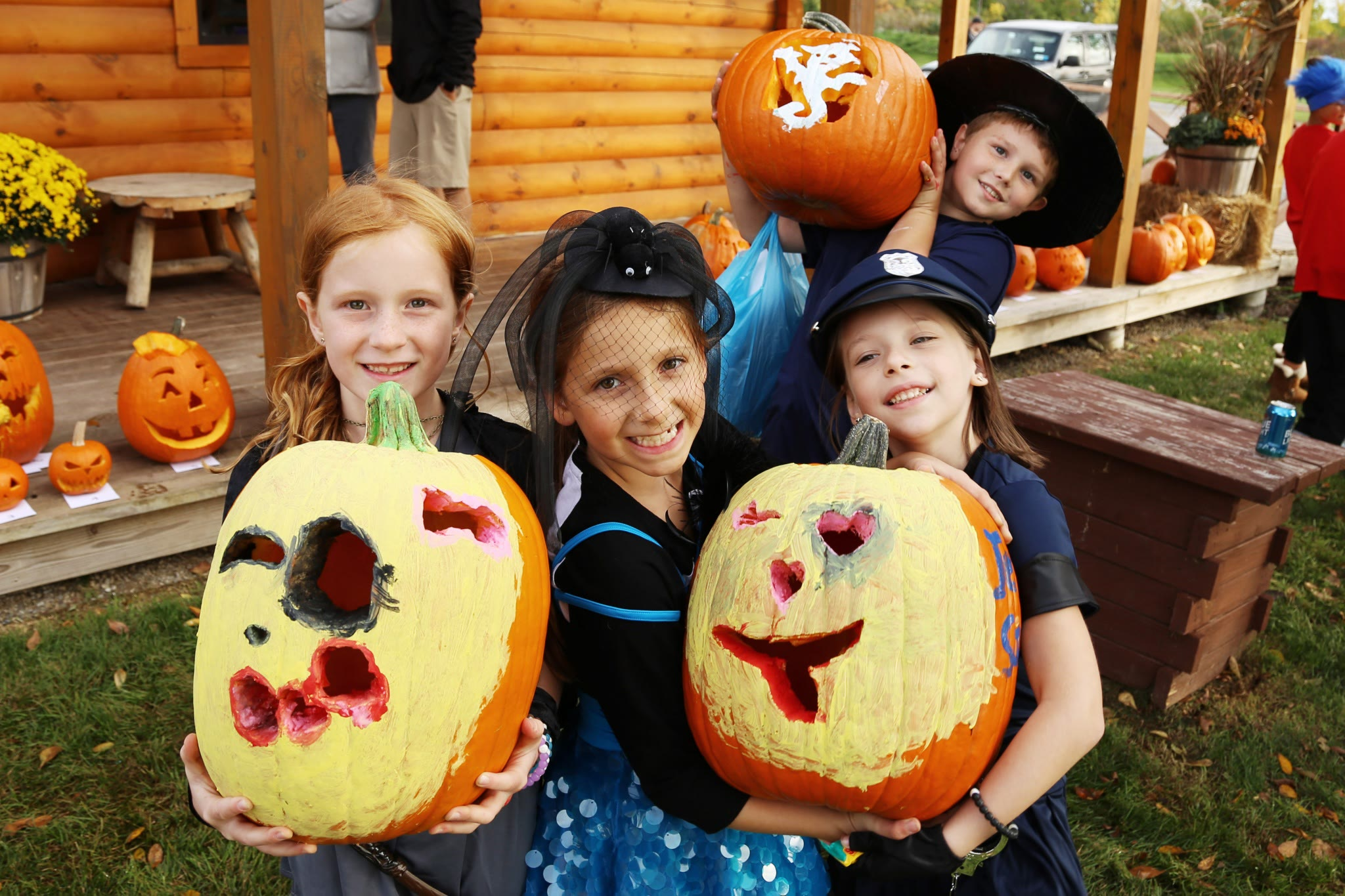 kids with decorated and carved pumpkins