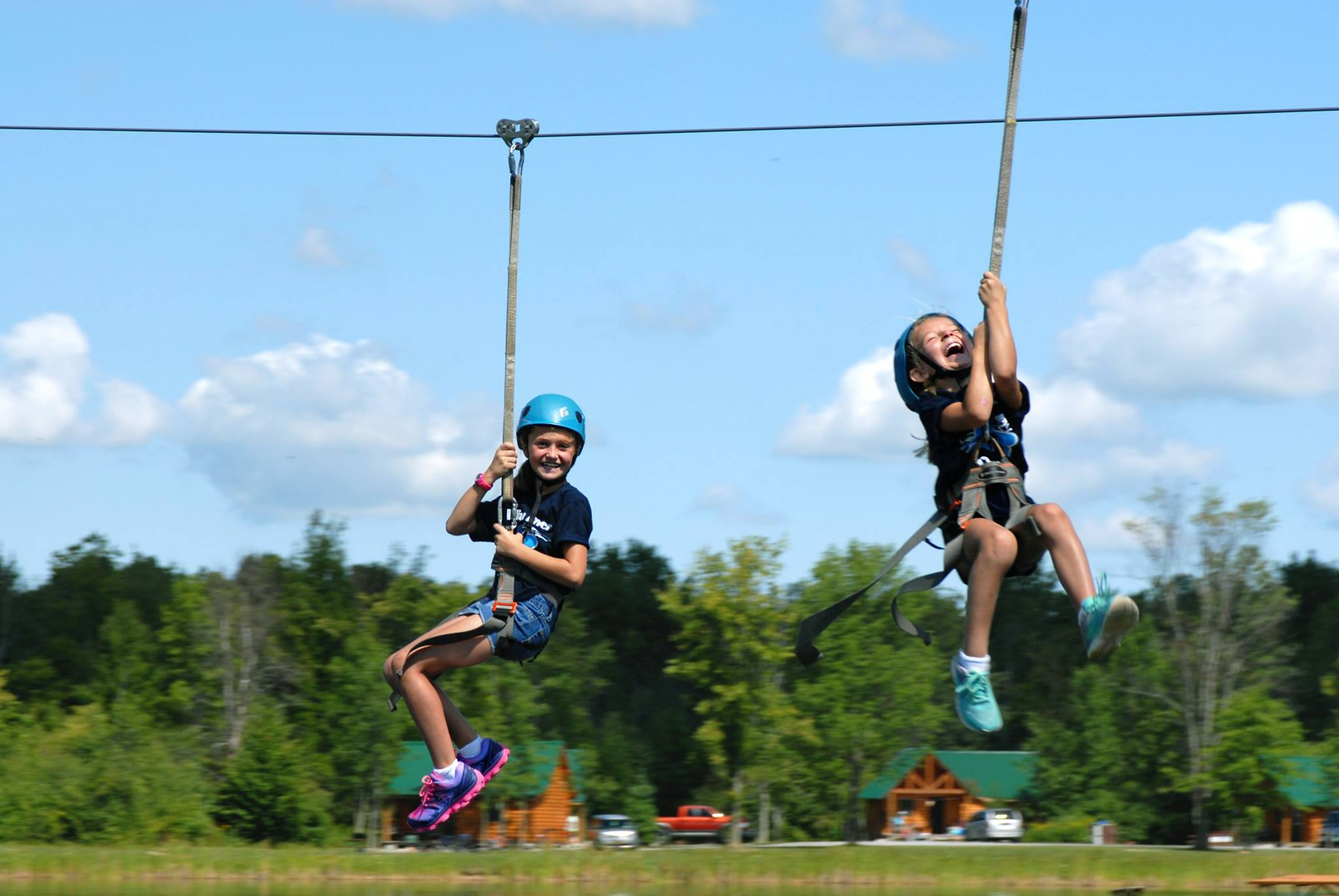 two children laughing on while on a zipline