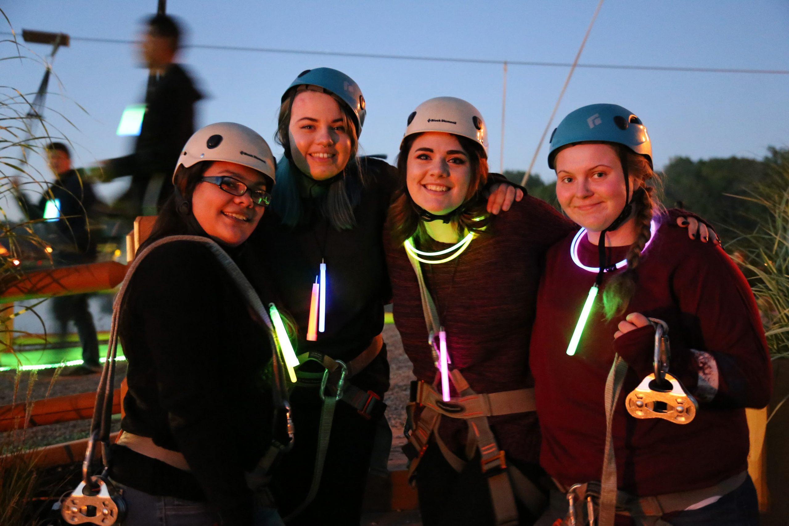 girls wearing helmets and glow sticks after zipline