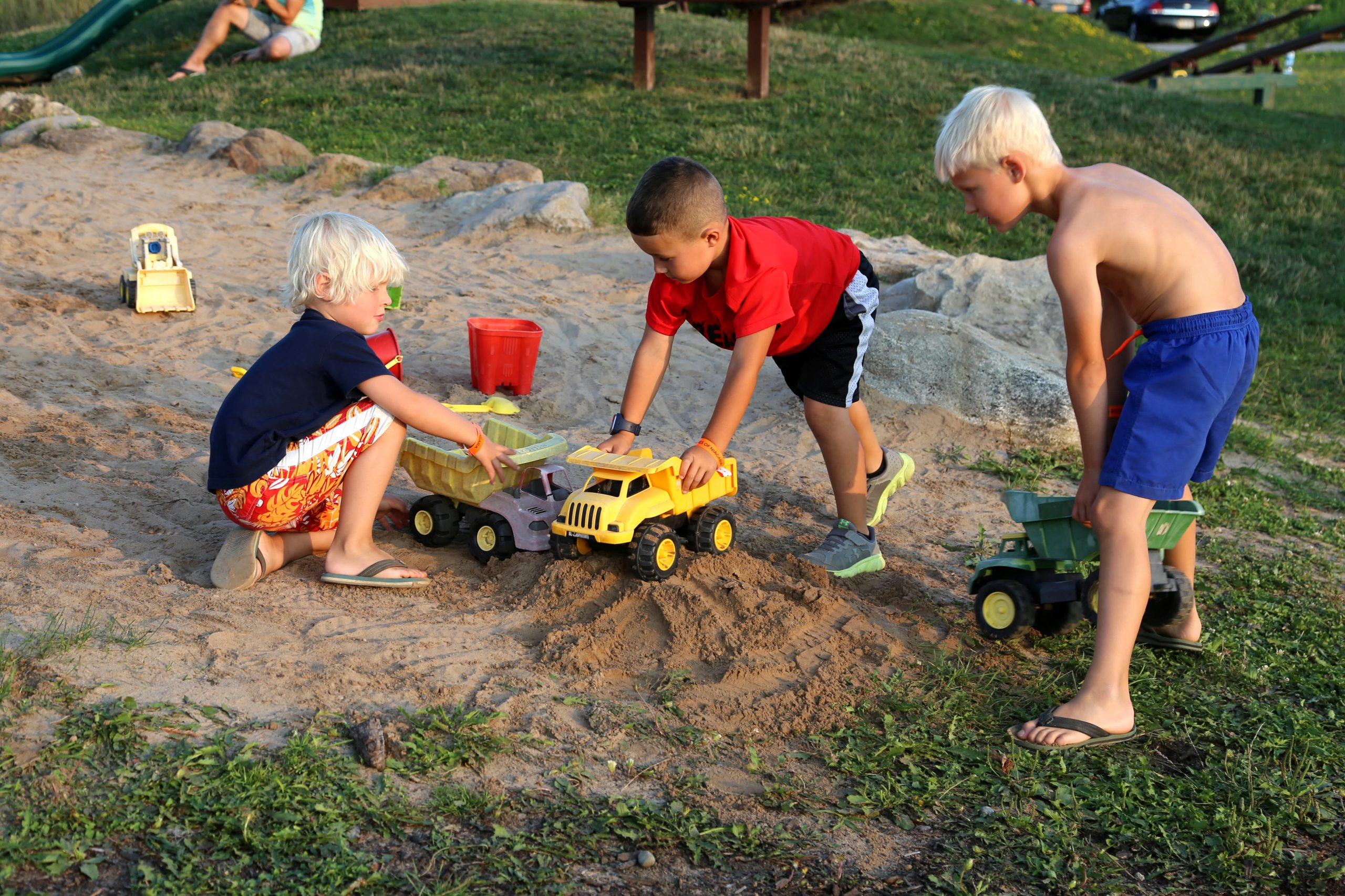 boys playing with trucks in sand pit