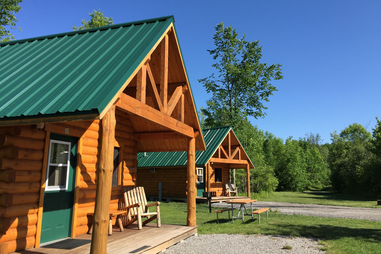 Two wood log cabins with green roofs