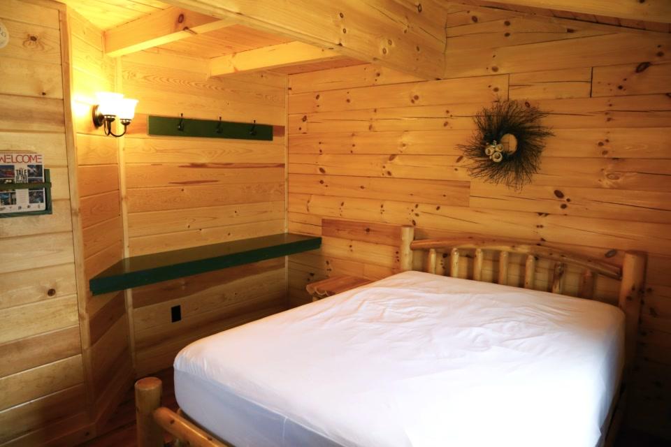 deluxe plus bedroom with queen bed and shelf