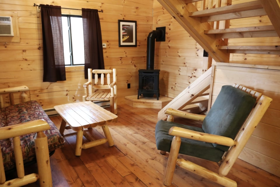 deluxe plus cabin living room with fireplace and log furniture