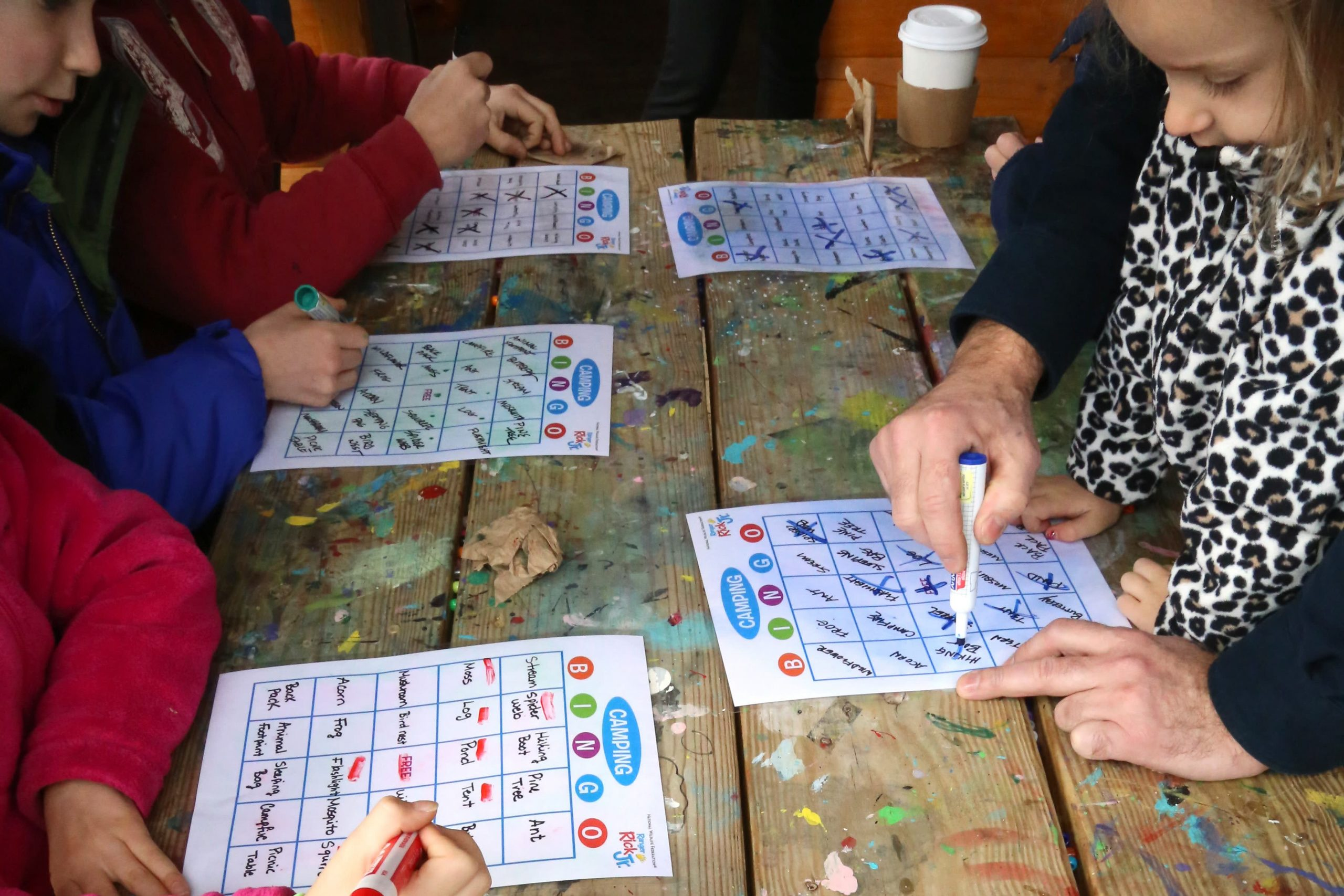 kids writing on bingo cards at picnic table