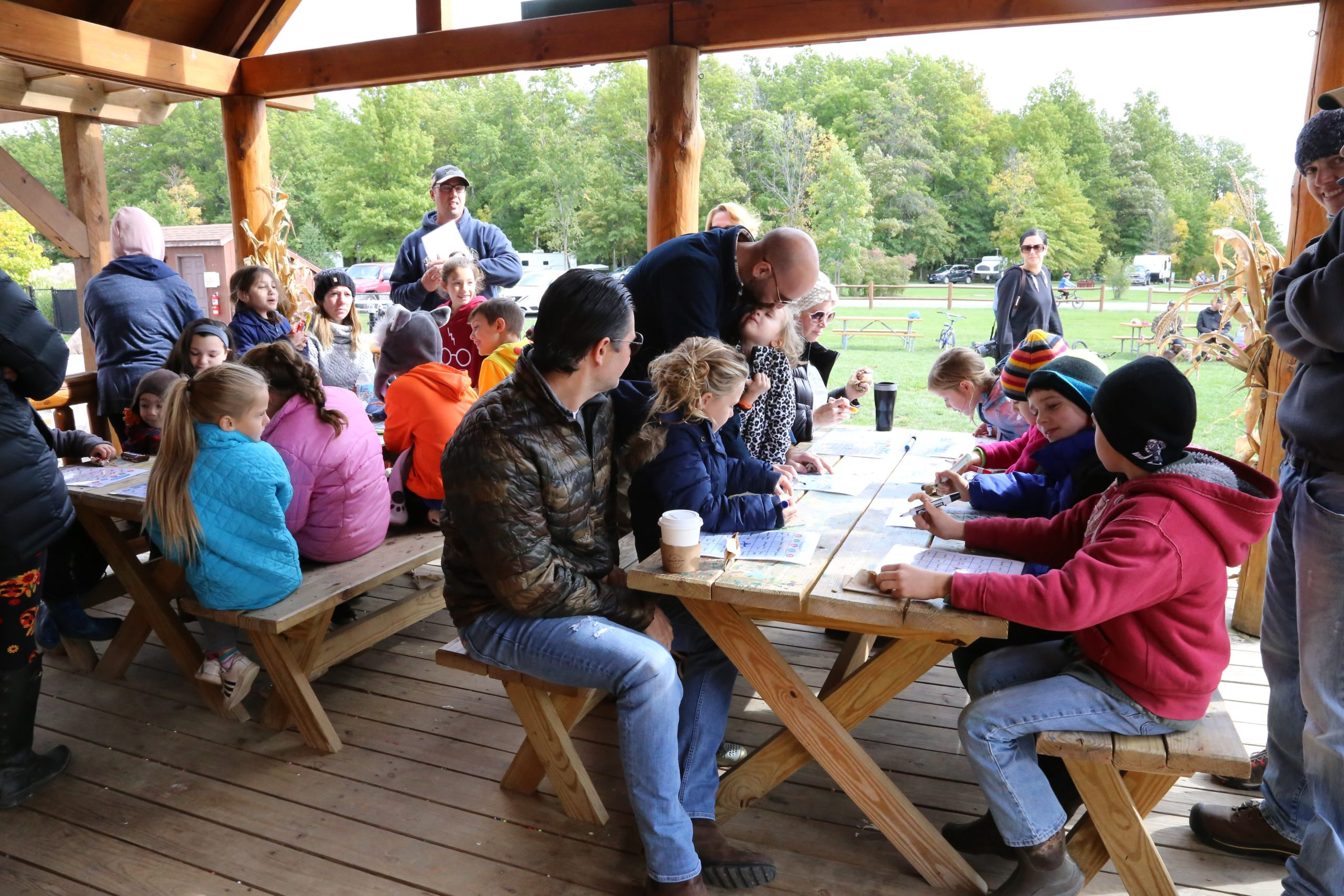 Adults and Children sitting on picnic tables playing bingo