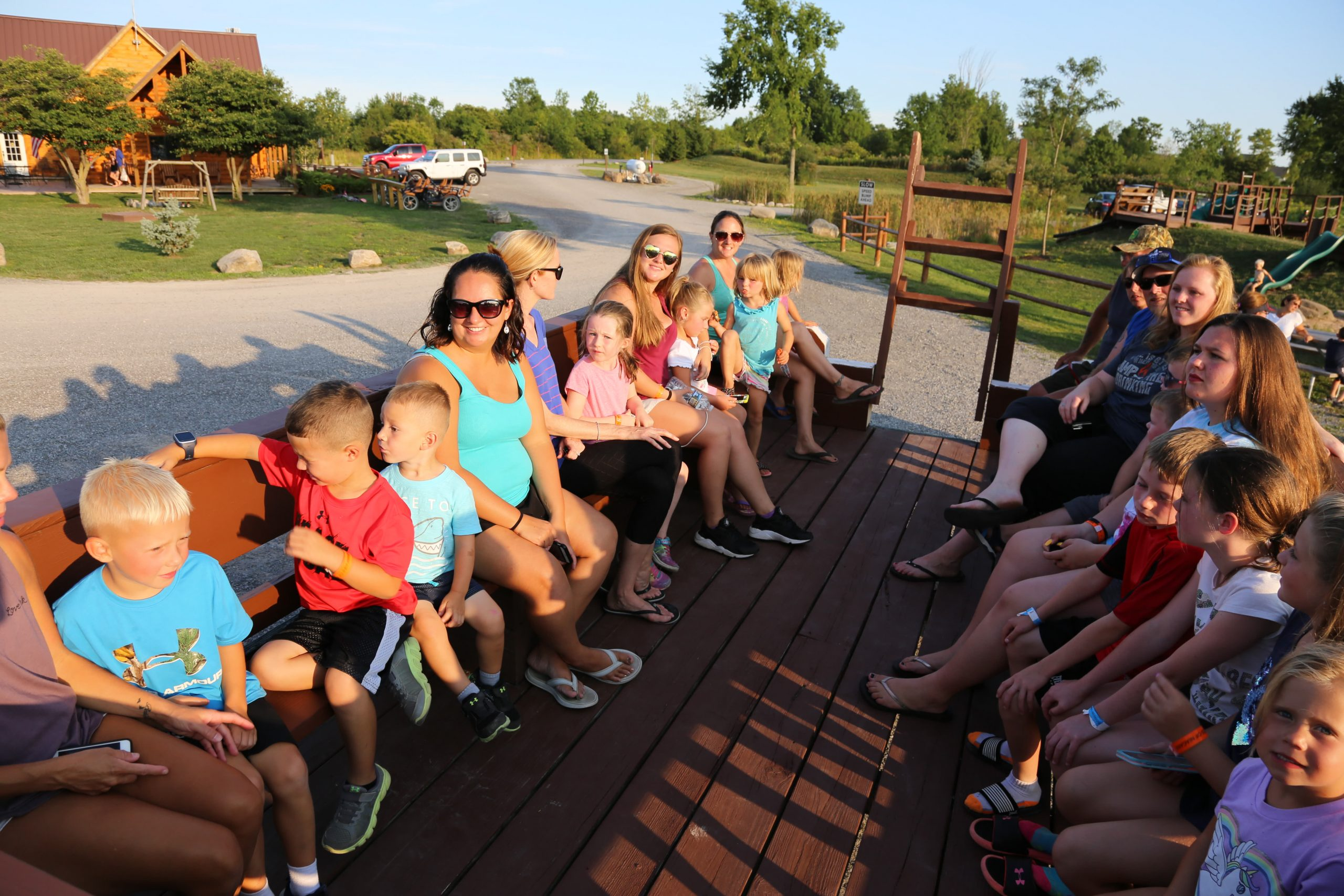 kids and adults sitting on wagon
