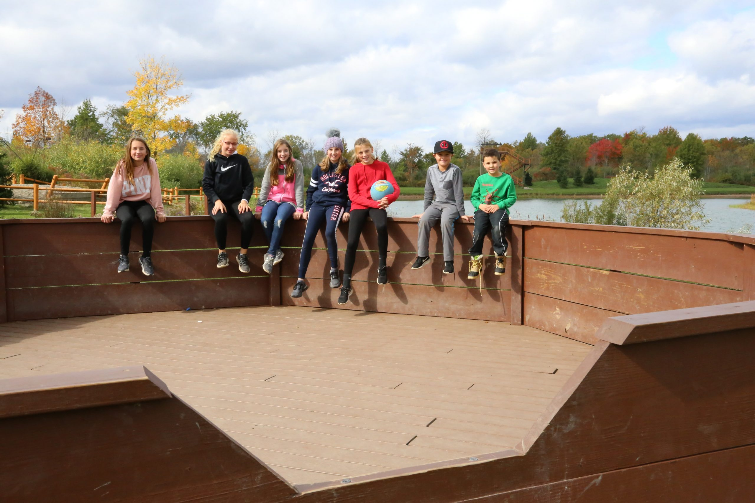 kids sitting on edge of gaga ball pit with ball