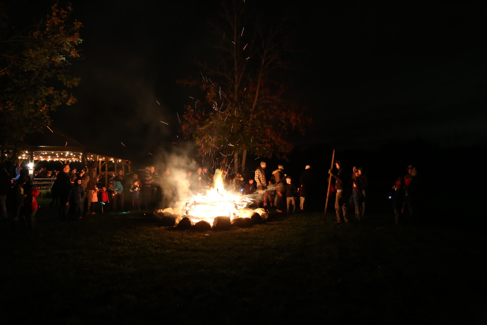 group standing around bonfire at night
