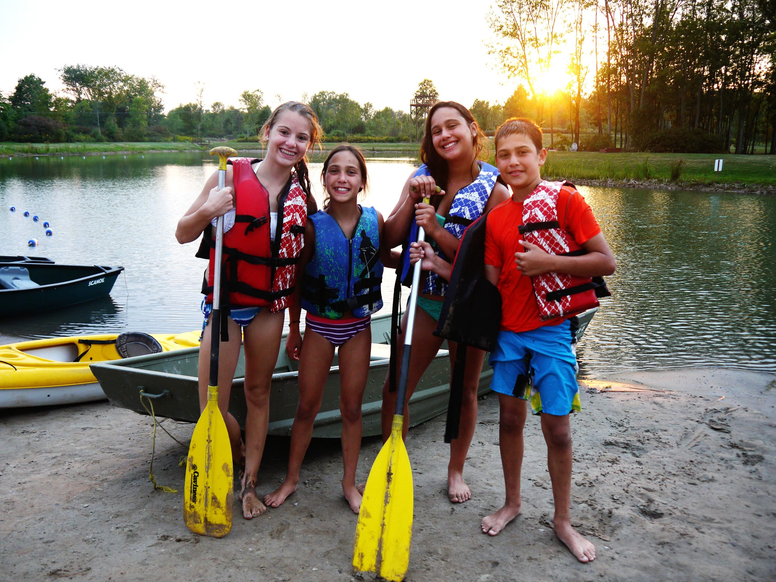 kids with life jackets and canoe paddles standing on the beach