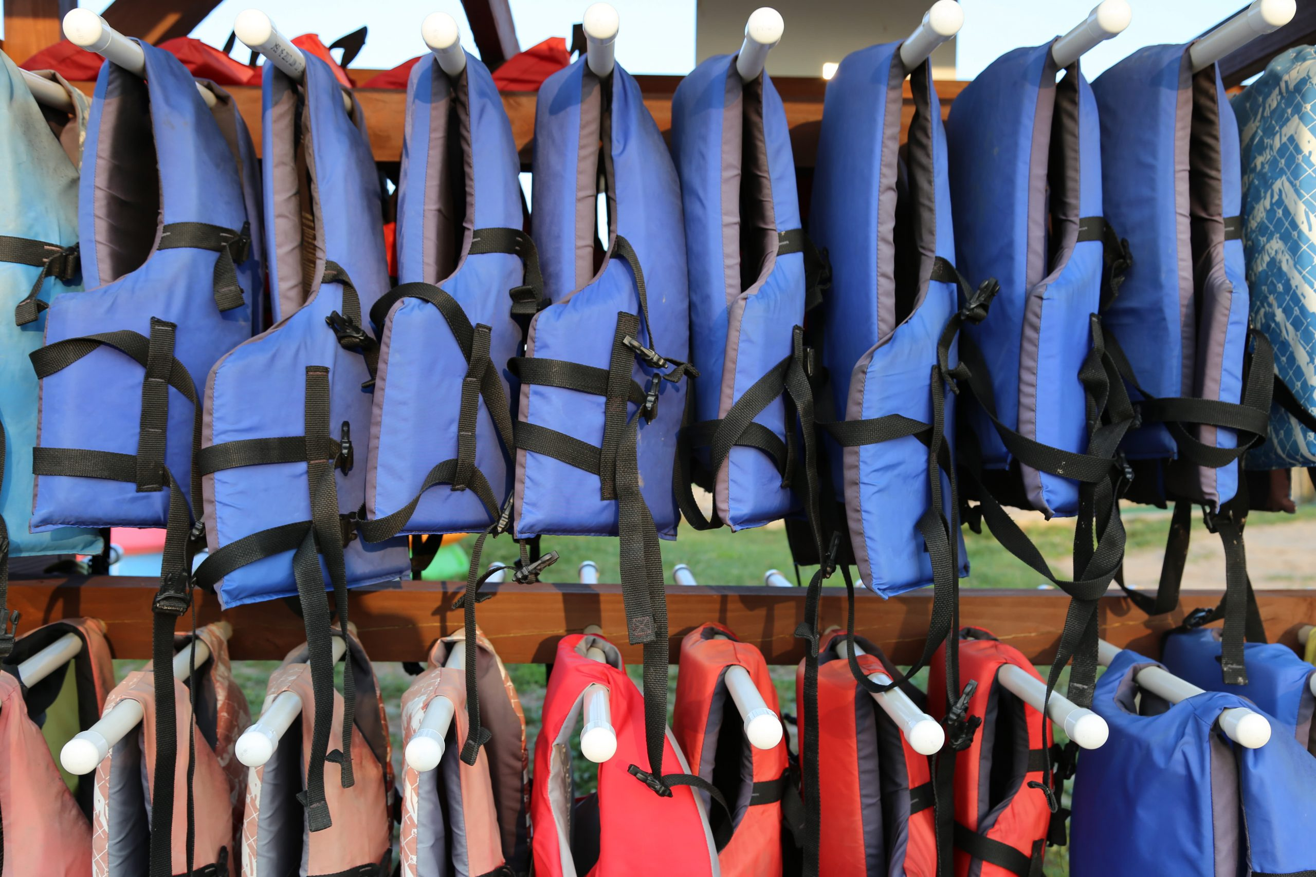 blue and red life jackets hanging on rack