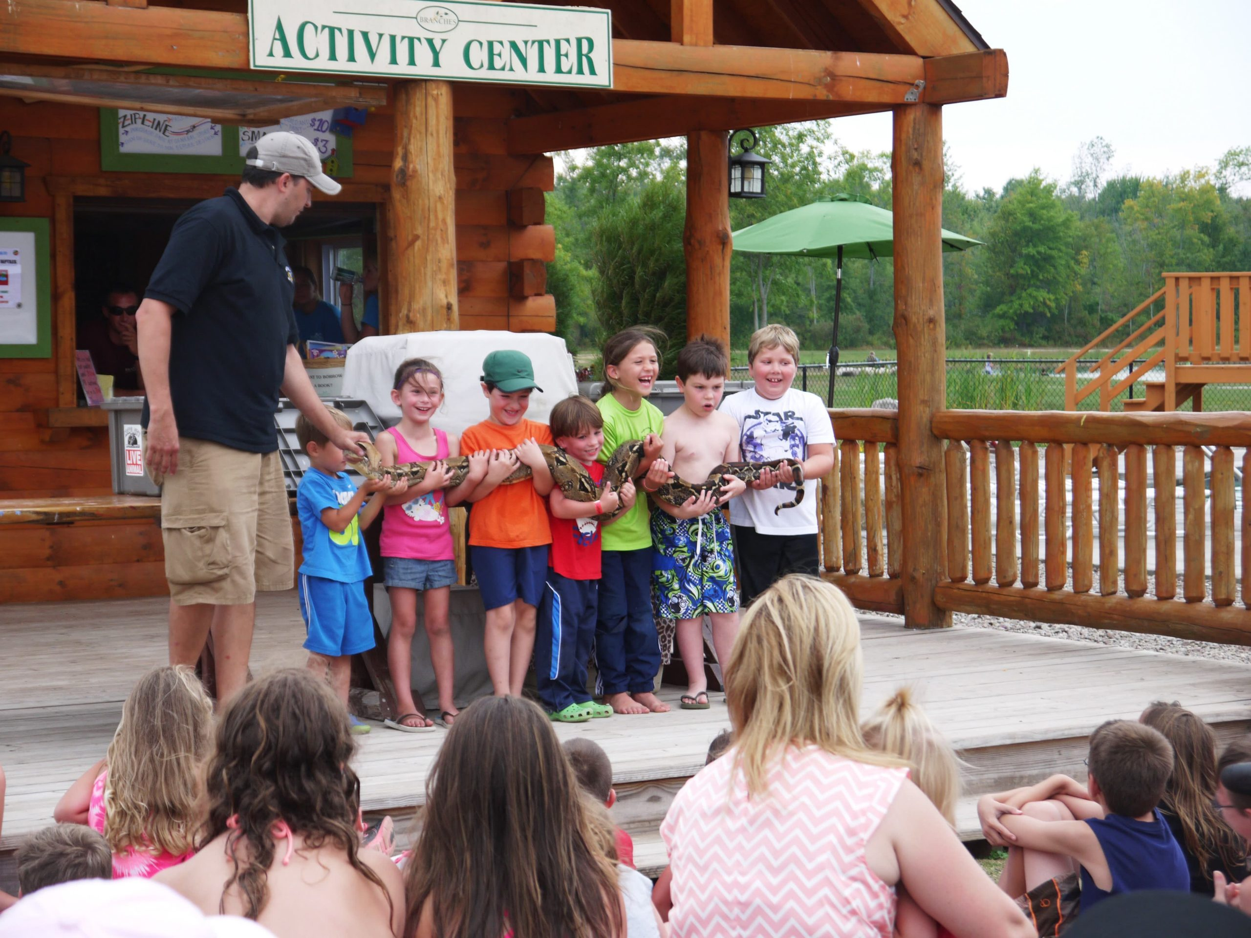 kids holding long snake at wild life show in front of log building