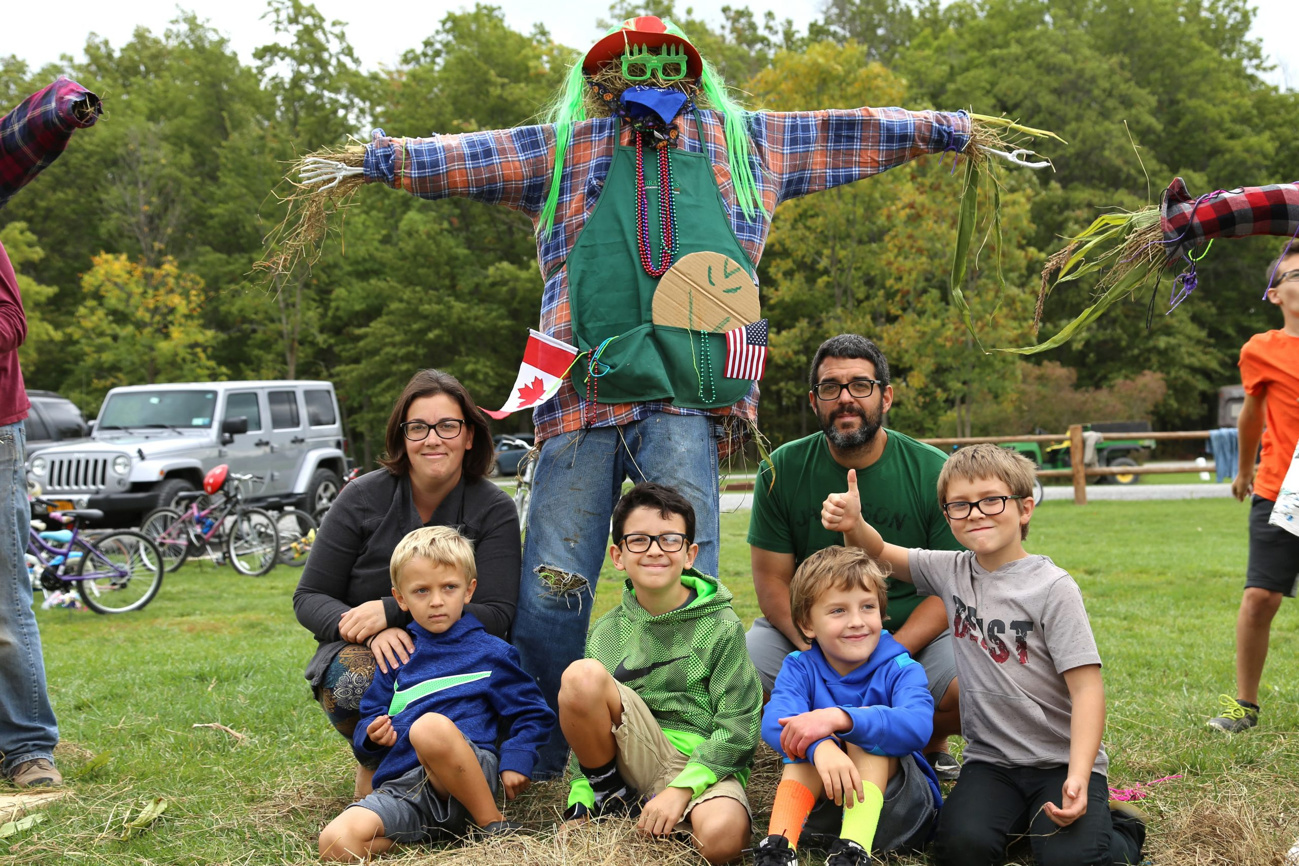 parents and kids with scarecrow