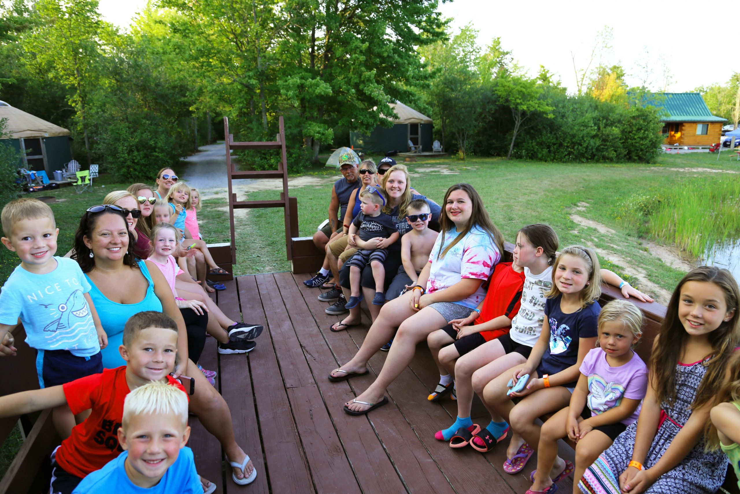 kids and adults riding on wagon ride through trees