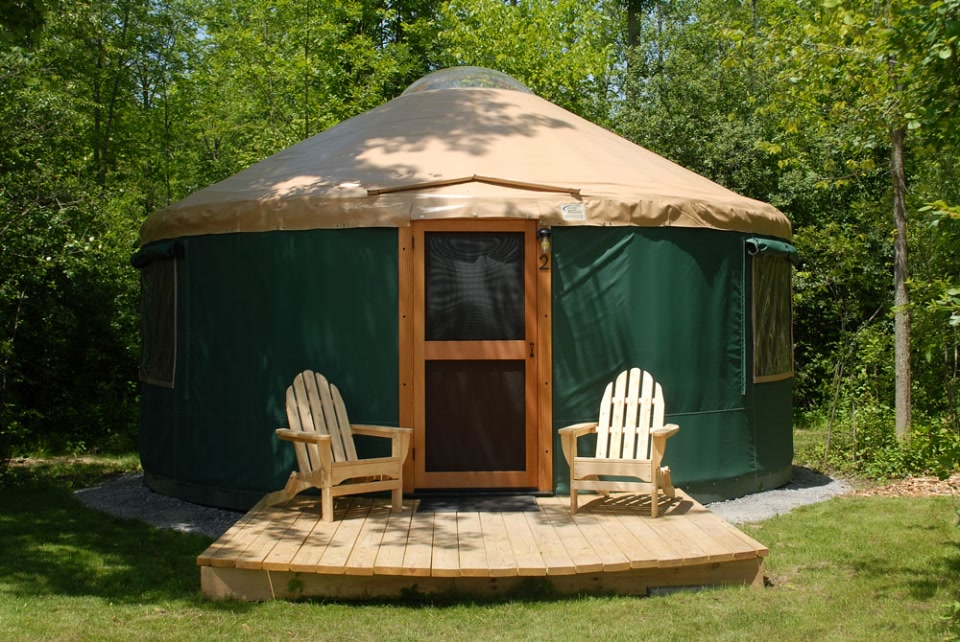 green and tan yurt with Adirondack chairs
