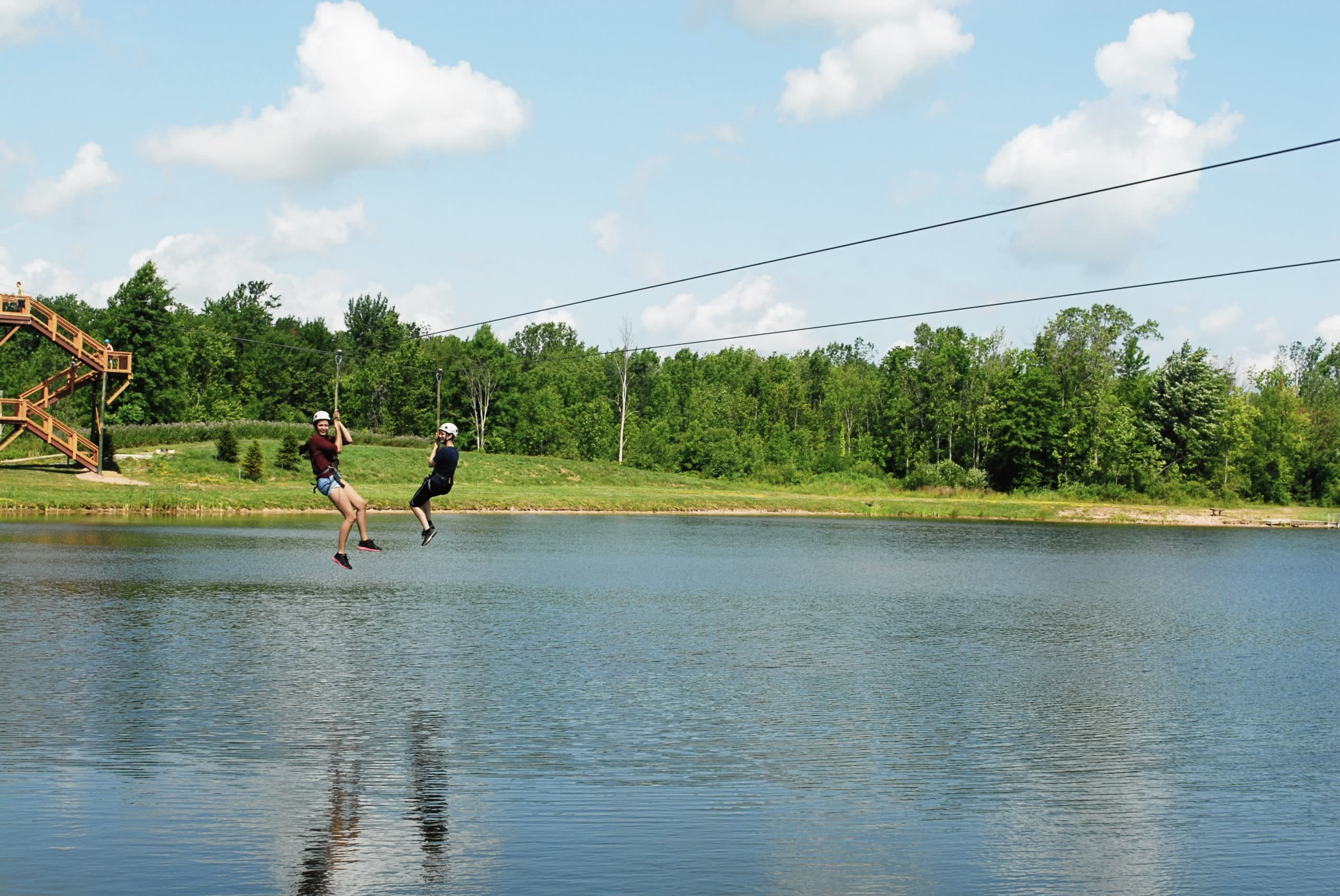 2 girls riding on zipline over the water